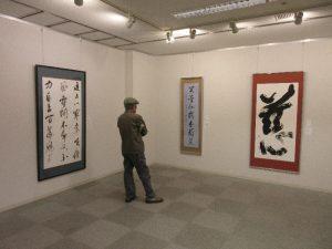 壁に展示されている書を鑑賞する人